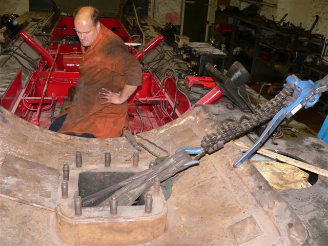 Neal Woods staring at the rear mounting holes. The pullift is being used through the exhaust pipe to pull the the cylinder against the frames. - Terry Newman