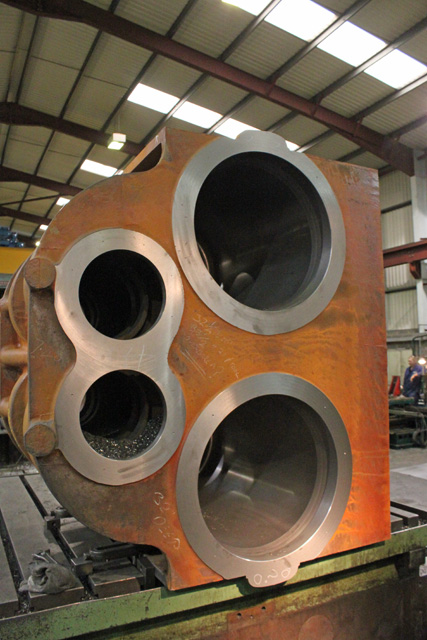 The freshly machined cylinder face showing the boring of the piston and valve openings.
