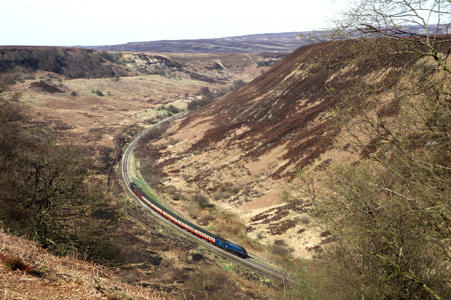 The size of an A4 pacific No 60007 Sir Nigel Gresley is dwarfed by the Newtondale Gorge as it brings the 14:30 Grosmont Pickering train down from the summit , banked by B1 61002 Impala (61264)- Maurice Burns