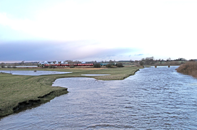 The view from the road bridge of the swollen River Swale which had burst its banks with the water level close to the bridge spans. After the train stopped just before the bridge Joem restarts for Leeming with its very last train of 2013 - the 14.30 Santa Special - Maurice Burns