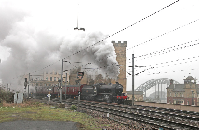 The K1 brings the empty coaching stock from Heaton into Newcastle Central station passing the Castle Keep. In the background is the Tyne Bridge and significantly the Bridge Hotel where the owners of 62005 had there very first meeting in October 1966 - Maurice Burns