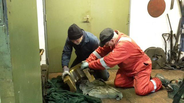 Brian Armstrong and Ian Pearson wrestle the axlebox back in to the workshop. - Nigel Hall