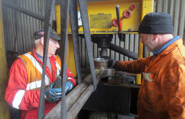 Ian Pearson and Brian Armstrong position rod and brass on the hydraulic press in the repair shed - John Hunt