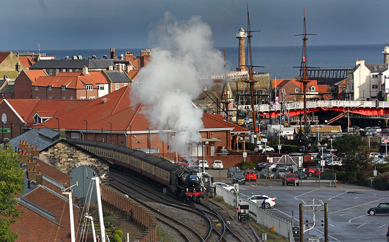 The K1 departs Whitby with the 10.00 for Pickering. piers, lighthouses and swing bridge in te background - Maurice Burns