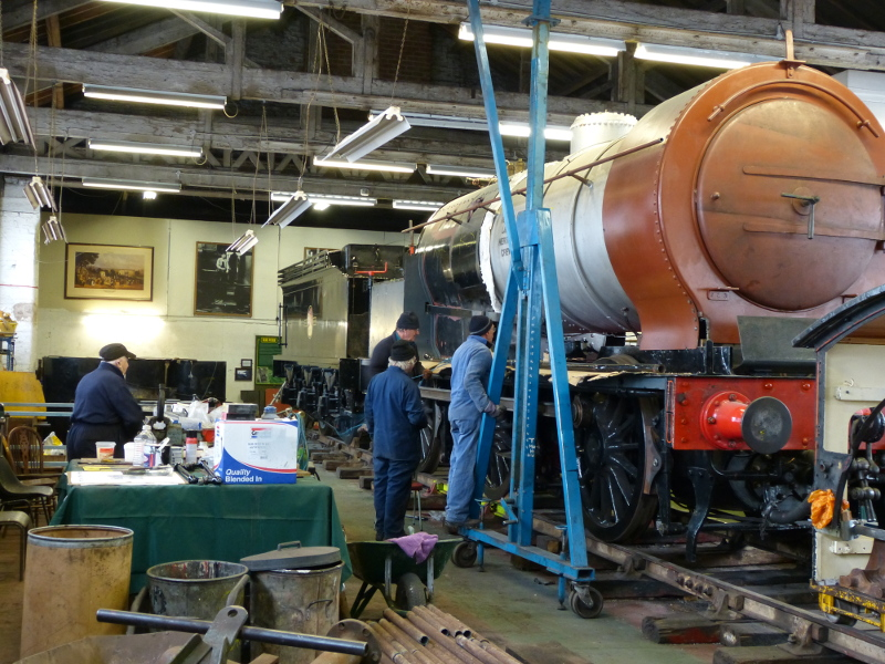 Derek Shorton refurbishes the J72 blower ring whilst Tim Wilkinson, Arthur Jenkins and Steve Johnson check the security of the ejector exhaust pope on the J27 running board - Terry Newman