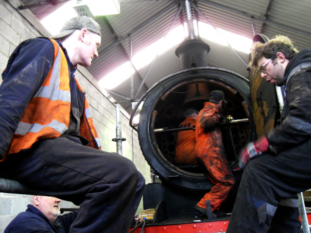 Alan Hardie and Mark O'Brien await the tube being extracted from the smokebox by Andy Lowes and Trevor Wilford - Joan Lowes